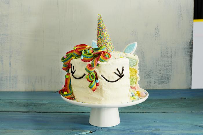 hier ist eine weiße torte mit einer regenbogenfarbenen mähne und mit einem großen bunten horn und mit kleinen blauen ohren