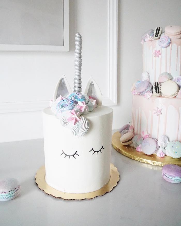 weißes einhorn mit schwarzen augen, einer mähne mit weißen und blauen rosen und kleinen weißen ohren - idee zum thema einhorn kuchen