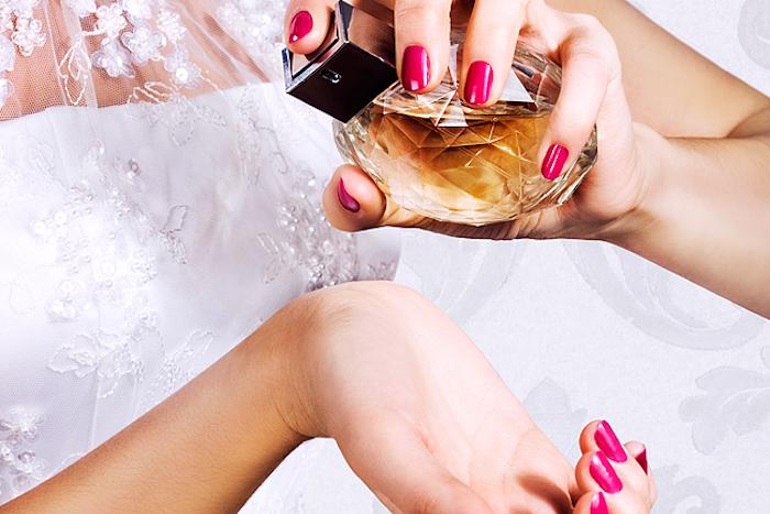 parfüm für dich, braut mit weißem hocheitskleid mit spitze, parfüm sprühen