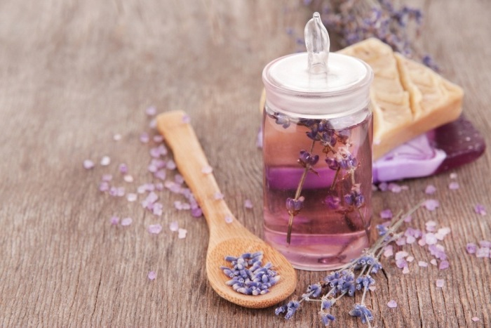 parfumöl mit lavendel, hölzerner löffel mit lavendelsamen, bio-kosmetik