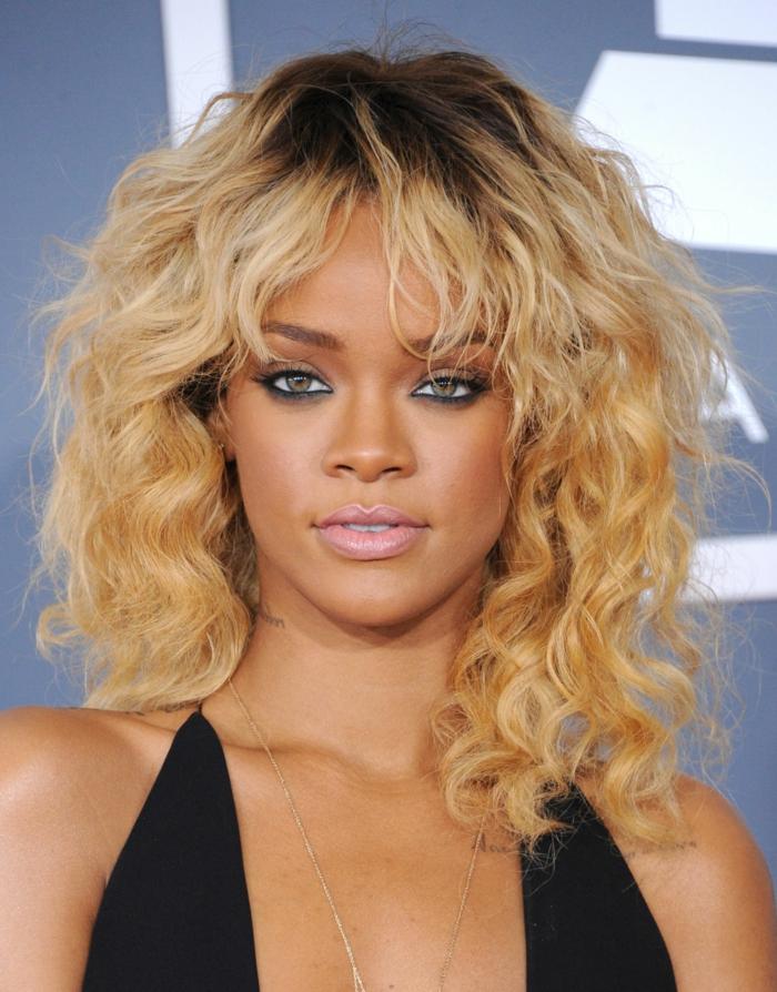 Rihanna mit Pony Frisur, dunkelblonde Locken, matte Lippen und schwarze Mascara, schwarzes Abendkleid