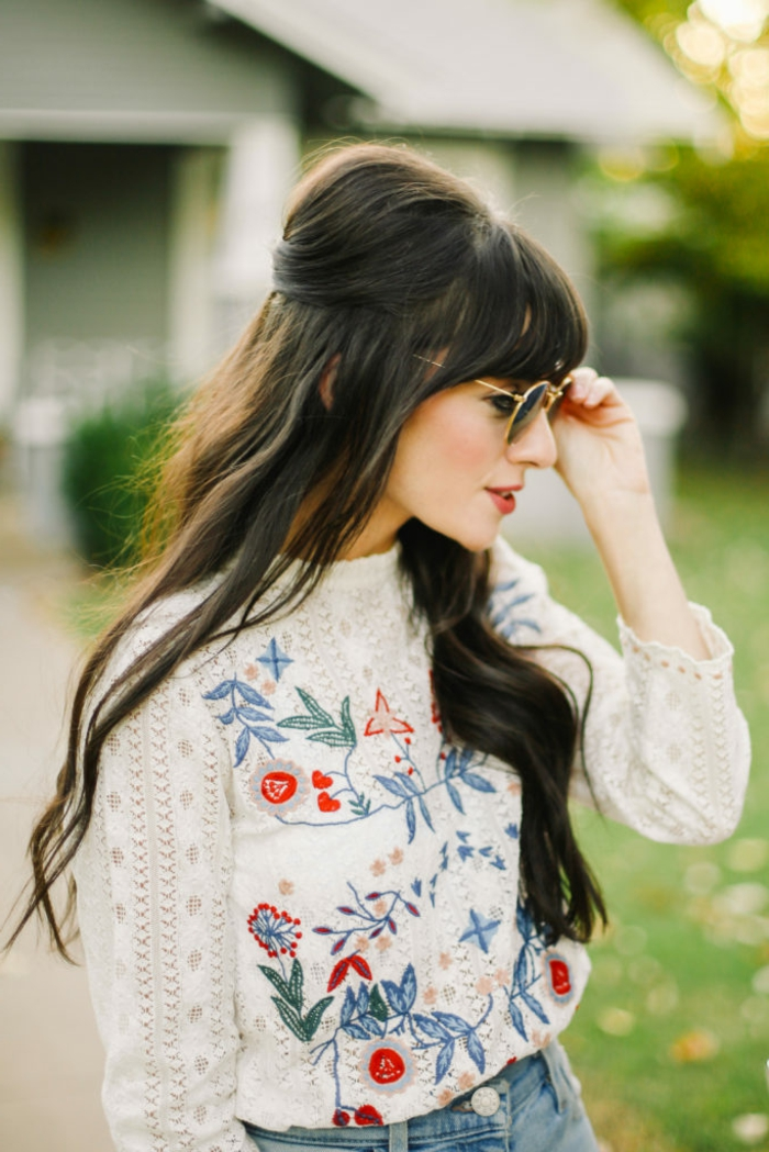 Lange schwarze Haare mit Pony, weißes Top mit Blumenmuster, rote Lippen und Porzellanteint