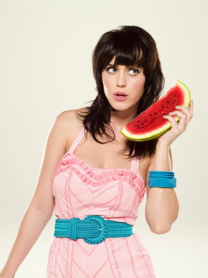 Pony Frisur in Retro Stil, rosafarbenes Kleid mit blauem Gürtel, rosafarbener Rouge und Lippenstift, Wassermelone als Handy
