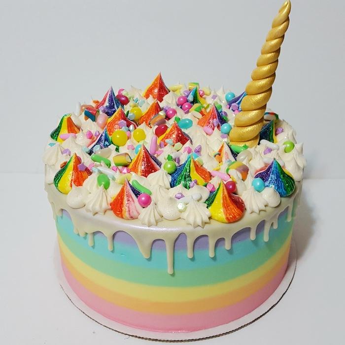 noch eine regenbogenfarbene torte mit einer weißen sahne und einem großen langen goldenen horn - idee für einhorn kuchen deko