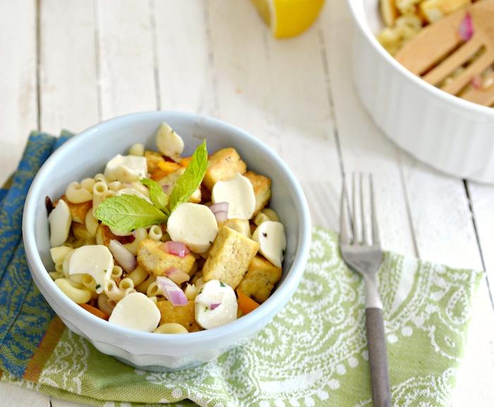 geräucherter tofu salat mit pasta frische blätter grünsalat kleine stücke frischkäse in schüssel serviert gabel tuch