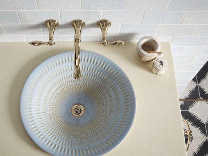schlichtes Badezimmer-Waschbeckendesign in Hellblau und Goldfarbe, goldener Wasserhahn, hellgelber Waschbeckentisch
