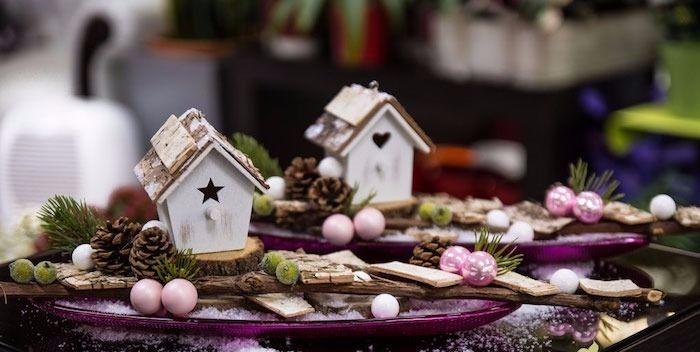 zwei hölzerne Häuser mit Löchern in der Form eines Sternes und eines Herzens, dekorative Glasteller in Violettfarbe, Deko mit Zapfen und Tannenbaumzweigen, Glastisch, dekoriert mit künstlichem Schnee