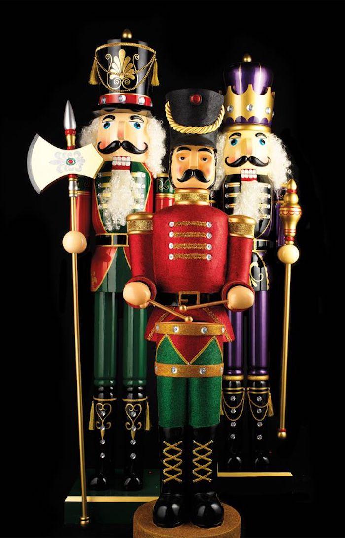 drei Nussknacker aus Holz und Plastik, drei Männerfiguren mit Hüten, Nussknacker mit Trommel, Nussknacker mit Achse, Nussknacker mit Zepter, Foto mit schwarzem Hintergrund