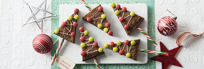 Triangelkuchen aus Schokolade mit Zuckergussdeko, rote und grüne Zuckerperlen, Lutscherstangen, zwei rote Weihnachtkugeln mit silbernem Glitzer, roter Stern aus Plastik, Tischdecke in zwei Farben mit Relif