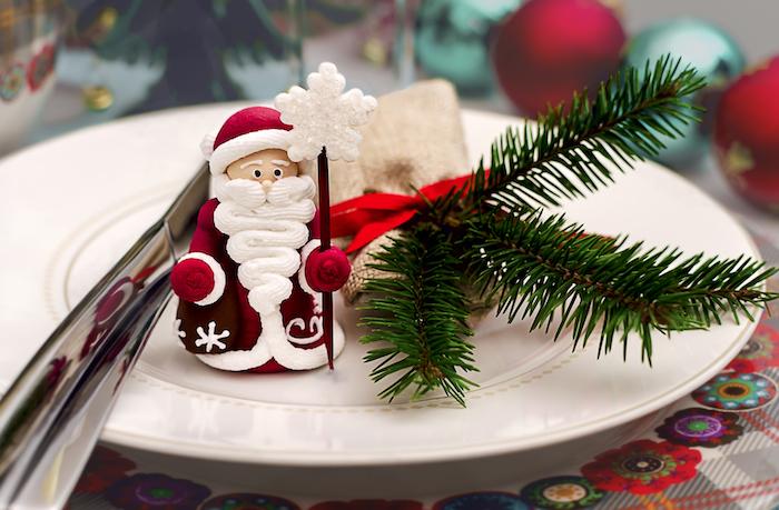kleine Weihnachtsmannfigur, weiße Porzellanteller mit gelben Punkten, kliener Tannenbaumzweig mit einer roten Schleife, Tischdecke mit Karomuster und Blumenprint