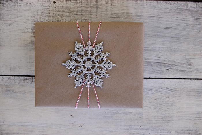 Basteln Winter - ein Geschenk mit braunem Papier verpacken und eine silberne Schneeflocke als Dekoration