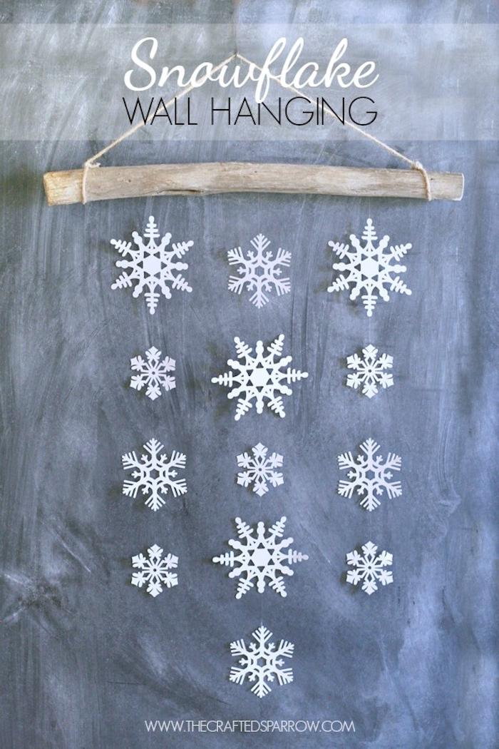 Basteln Winter - eine Wand aus weißen Schneeflocken von einem Stock hängend