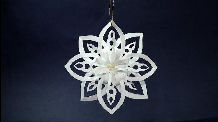 eine weiße Schneeflocke wie Blume in der Mitte, von Draht hängend - Fensterdeko basteln