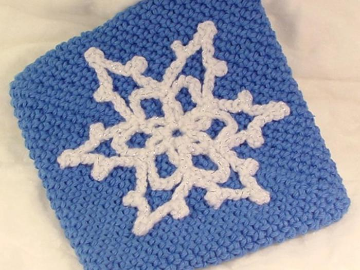 eine blaue gehäkelte Tüte mit einem weißen Schneeflocke als Dekoration - Schneeflocken Bilder