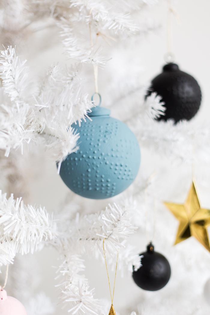 ein blaue Weihnachtskugel auf einem weißen künstlichen Weihnachtsbaum - Schneeflocken Bilder