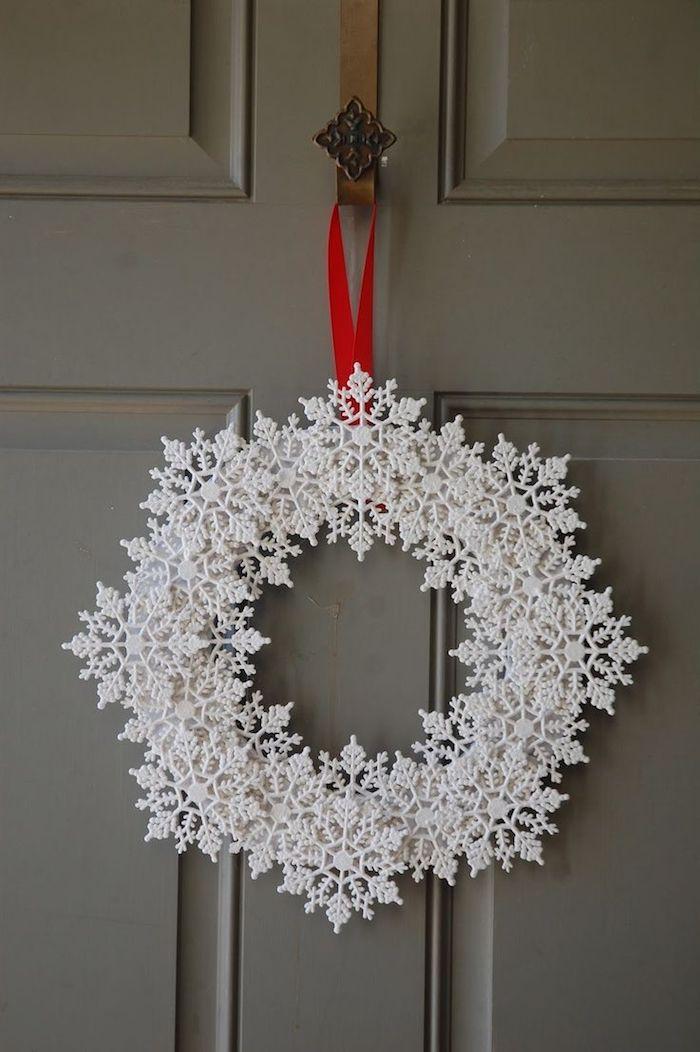 ein Türkranz zu Weihnachten in weißer Farbe mit einem roten Band befestigt - Schneeflocken Bilder