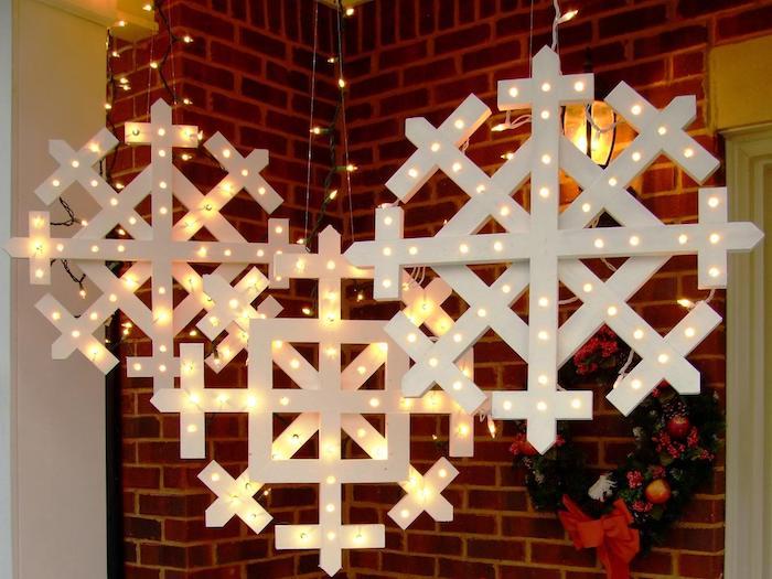 drei Schneeflocken mit leuchtenden Verzierungen aus dem Dach hängend - Schneeflocken Bilder