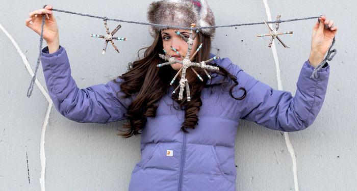 eine junge Dame hat Schneeflocken aus Stöckchen gebastelt - Fensterdeko basteln
