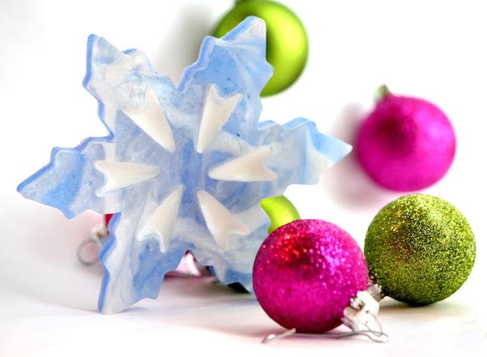 eine blaue Schneeflocke aus Wachs von Weihnachtskugeln umgeben - Schneeflocken Deko