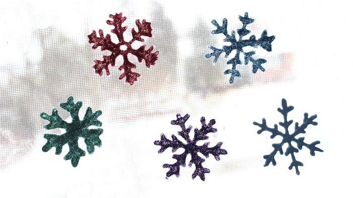 Fensterdeko basteln - fünf Schneeflocken in verschiedenen Farben - rot, grün und blau