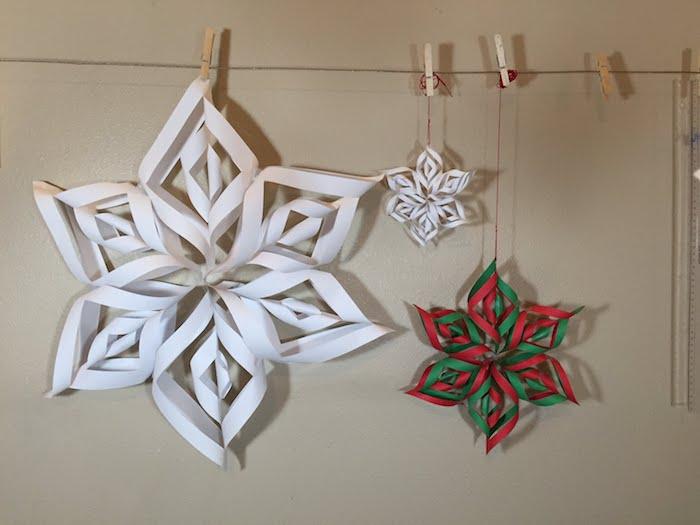 Schneeflocken aus Papier - zwei weiße Schneeflocke und eine bunte Schneeflocke