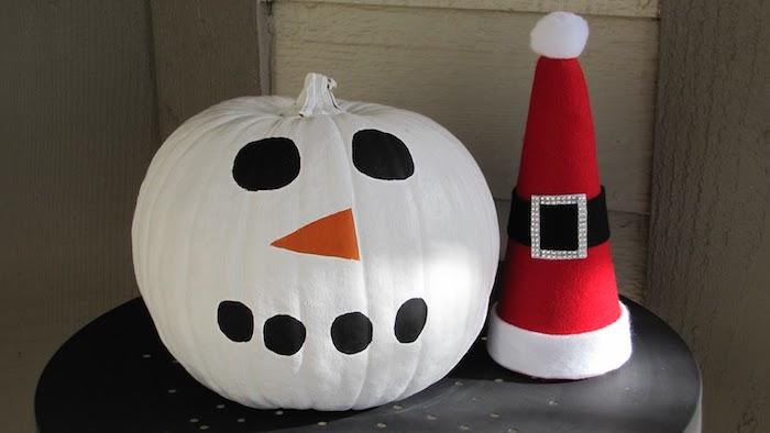 schneemann aus einem weißen kürbis - mit schwarzen augen, einer orangen nase und einem roten hut - schneemann basteln