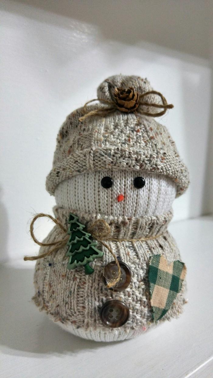 kleiner weißer schneemann aus einer weißen socke und mit schwarzen augen, braunen knöpfen, einem grünen Tannenbaum und einem grünen herzen