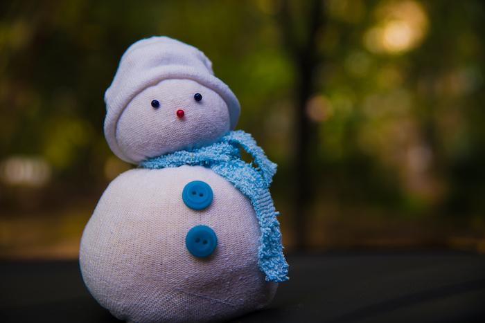 kleiner weißer schneemann mit zwei blauen knöpfen, zwei schwarzen augen und einem weißen hut - einen schneemann aus socken basteln