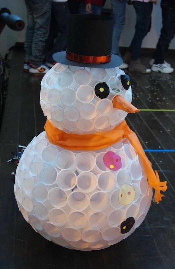 basteln schneemann - weißer schneemann aus weißen plastikpecher mit einer orangen nase, schwarzen augen und knöpfen
