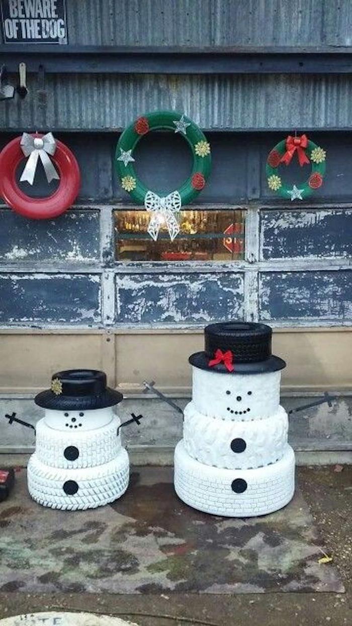 zwei große weiße schneemänner aus reifen und mit schwarzen hüten, schwarzen augen und schwarzen knöpfen