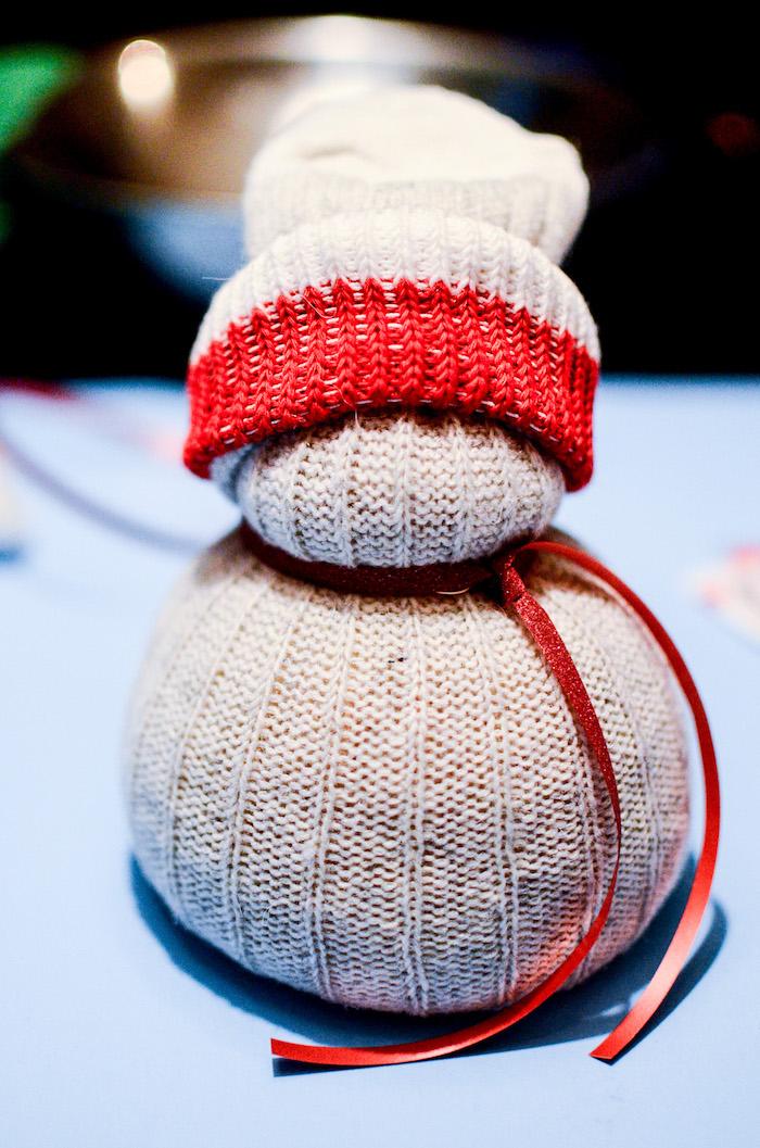 basteln schneemann - ein weißer schneemann aus socken und mit einem roten hut und einem roten schal