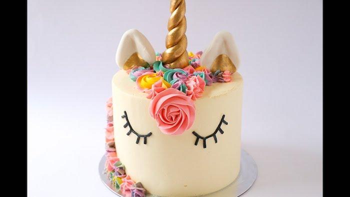 idee für eine weiße torte mit einem weißen einhorn mit schwarzen augen und pinken, gelben und blauen rosen und einem goldenen langen horn - ide für eine einhorn kuchen deko