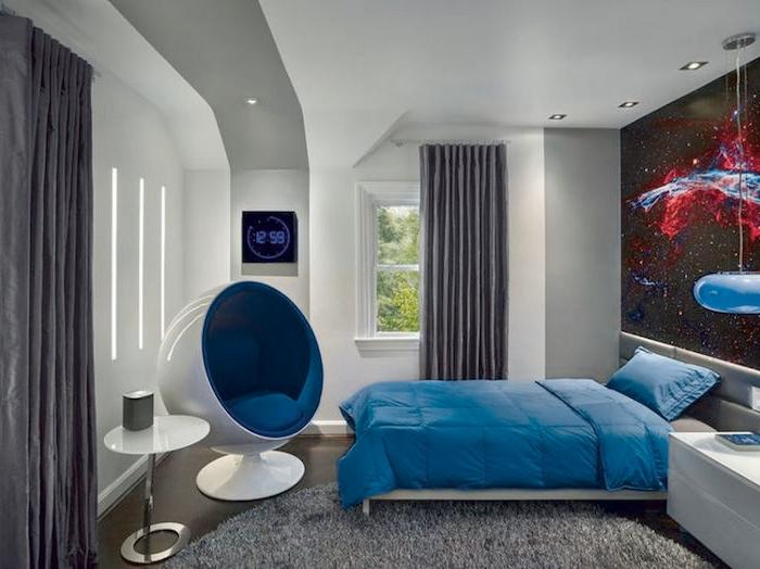 ein runder grauer Teppich, blaue Bettwäsche, weißer Tisch und ein moderner Sessel - Jugendzimmer gestalten