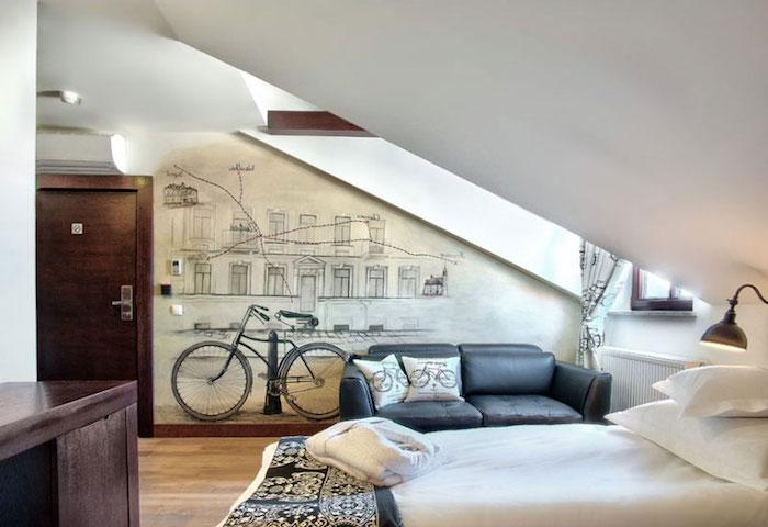 ein Zimmer für Teenager in Dachgeschosswohnung mit Fahrrad Wandtattoo, ein weißes Bett, Laminat-Boden