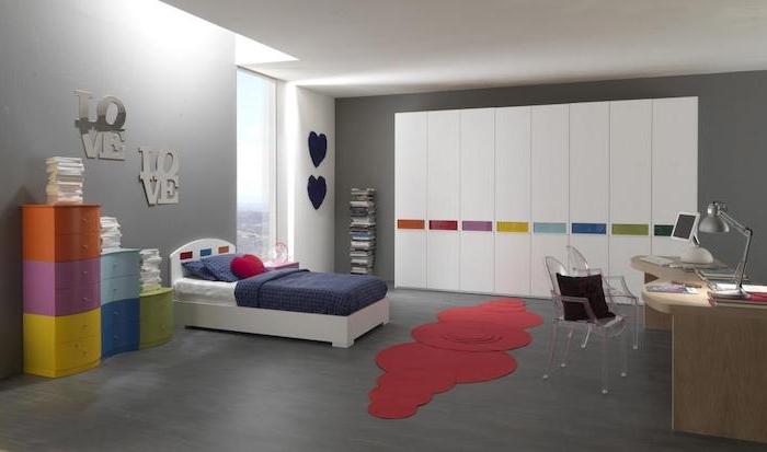 grauer Laminatboden, bunte Regale, roter Teppich mit ausgefallener Form, hölzerner Schreibtisch