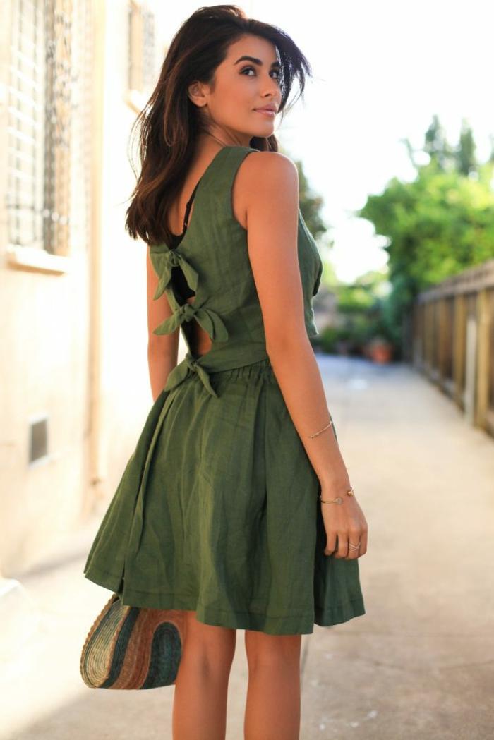 Grünes Kleid mit Trägern, lange schwarze Haare mit seitlichem Pony, matte Lippen und schwarze Mascara