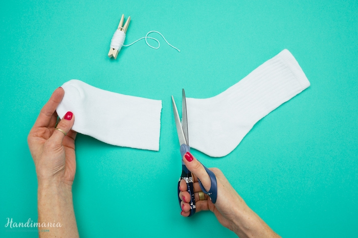 schneemann basteln anleitung - eine schere und eine weiße soche und zwei hände einer frau