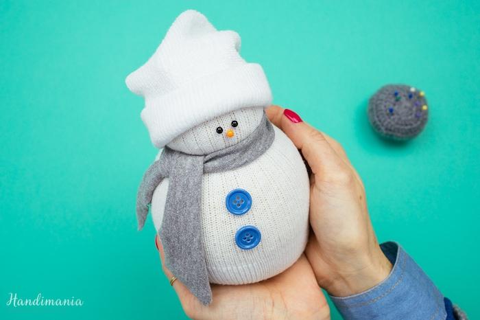 ein schneemann mit einem grauen schal, schwarzen augen, blauen knöpfen - schneemann aus socken basteln