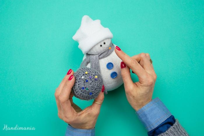 ein weißer schneemann mit einem grauen schal und zwei blauen knöpfen und schwarzen augen