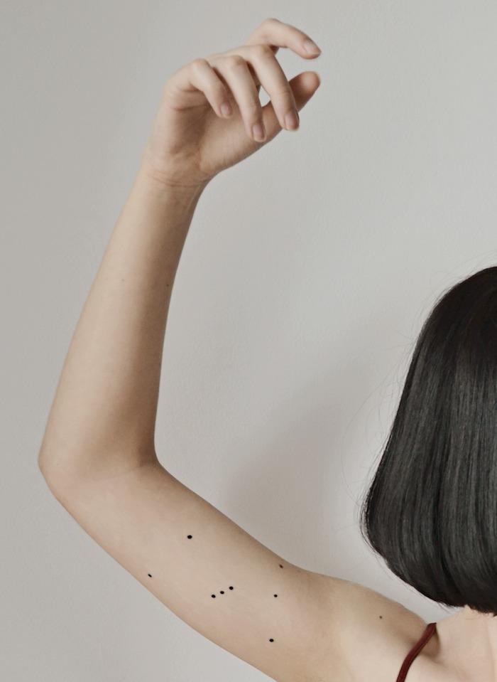 junge frau und eine winzoge tätowierung mit einem schwarzen sternbild mit kleinen schwarzen sternen - eine hand mit stern tattoo