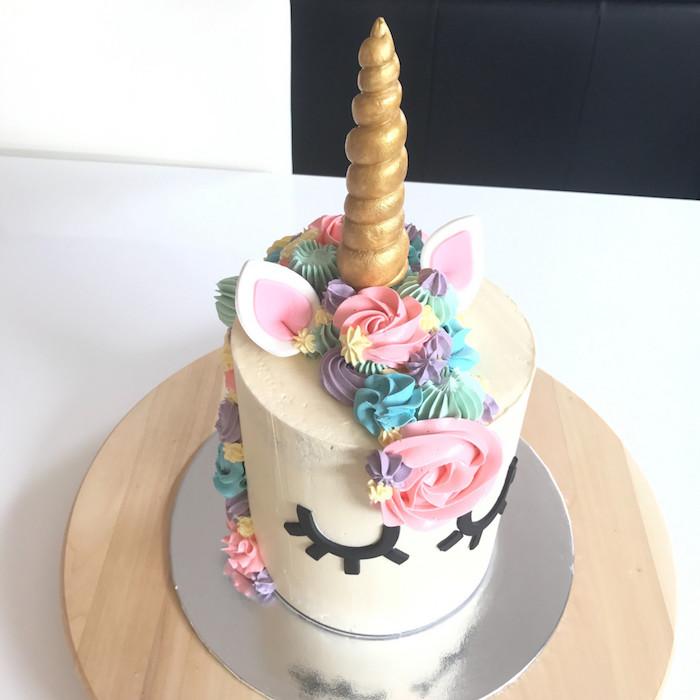 idee für eine weiße torte mit einem einhorn mit schwarzen augen, einer langen mähne und einem goldenen horn und großen pinken rosen und kleinen blauen und gelben rosen