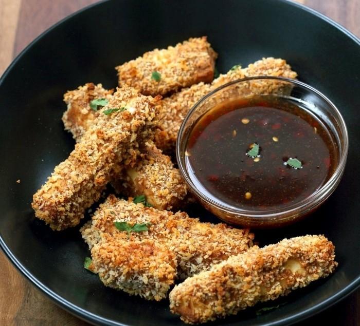 tofu zubereiten tofüstücke braten spezielle bratmischung müsli kornflakes kräuter chilli soße schwarze teller
