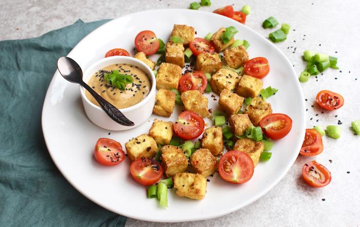 geräucherter tofu serviert in teller mit cherrytomaten und senfsoße als vorspeise schwarzer sesam