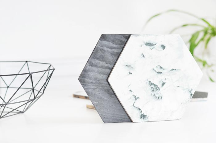 eine Holz- und einer Marmorplatte zum Servieren von kalten Anschnitten, dekorative Obstschüssel mit abstraktem Design, grüne Pflanze in der rechten Ecke des Zimmers