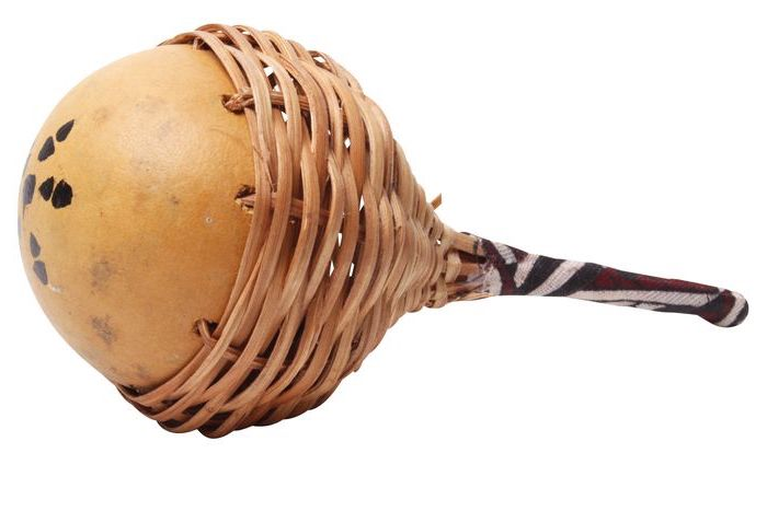 Rasseln aus Flaschenkürbis, der Stiel ist aus Holz und mit Stoff bezogen und an dem Flaschenkürbis mit Holzreimen befestigt
