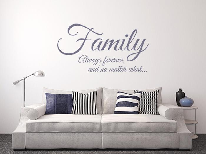 Wohnzimmer mit Wandtattoo, Wohnzimmer mir grauer Couch mit gemütlichen Couchkissen mit verschiedenen Musterbezügen, runder Beistelltisch mit drei Etagen in Weiß, zwei dekorative Vasen aus Porzellan in Blau und Schwarz, Stehlampe mit Metallkorpus in der linken Ecke des Wohnzimmers, Wohnzimmer mit грауем Мокетт