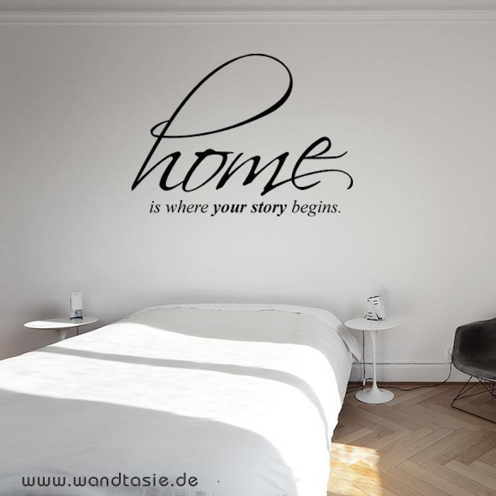 Wandtattoo auf Englisch - Home is where your story begins, Schlafzimmer mit einem Doppelbett mit weißer Schlafdecke, zwei runde Nachttische in Weiß, Schlafzimmer mit Parkettboden, schwarzer Lederstuhl mit Metallbeinen
