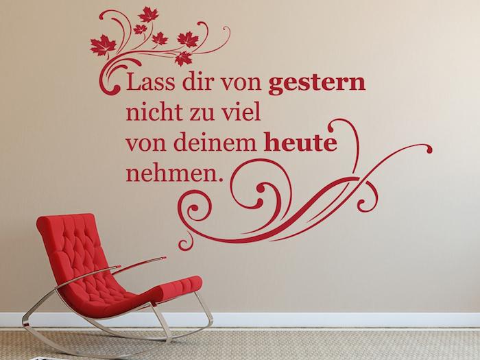 Umzugswünsche an einer Wand, gestrichen in Beige - Lass dir von gestern nicht zu viel von deinem heute nehmen, Wand mit roten Buchstaben beschriften, Wandtattoo mit roten Baumblättern, roter Relax-Stuhl mit Metallbeinen, Polster-Schaukelstuhl in Rot mit metallen Armlehnen