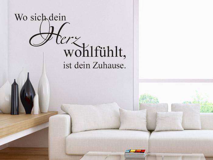 Wohnzimmer mit weißer Couch mit kleinen weißen Kissen, Couchtisch aus Glas mit viereckiger Form, ein Haufen Bücher mit bunten Umschlägen auf dem Wohnzimmertisch, Holztisch mit weißen Beinen und vier dekorativen Vasen darauf, großes Fenster mit Gartenaussicht hinter der Couch