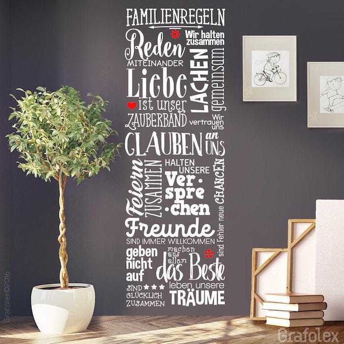 Sprüche zur Einweihung, eine Liste mit Familienregeln, aufgezählt und an der Wand mit weißen Buchstaben mit unterschiedlicher Schrift geschrieben, zwei kleine rote Blumen und ein kleines rotes Herz an einer lila Wand, ein Haus mit Parkettboden und Holztreppen, zwei Zeichnungen von einem Jungen mit einem Fahrrad und einem Skateboard, ein eingepflanzter Baum mit großer grünen Krone in einem großen weißen Pflanzenopf, platziert in der linken Ecke des Flurs, ein Haufen Bücher am Boden